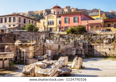 Remains of the Library of Hadrian, Athens, Greece. It is one of the main landmarks of Athens. Scenery of the Athens centre with ancient Greek ruins in summer. Acropolis of Athens in the distance.