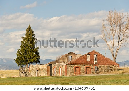 Remains of two-story brick and stone house after a fire - stock photo