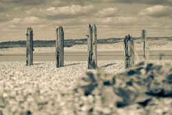 Remains Old destroyed pier on stony beach along Rother River and Rye Nature Reserve split toned for old-world effect.