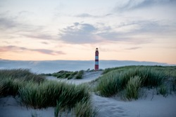 Remarcable light house of Amrum (Oomram) in Northern Germany at the Northern See at sundown with redish sky