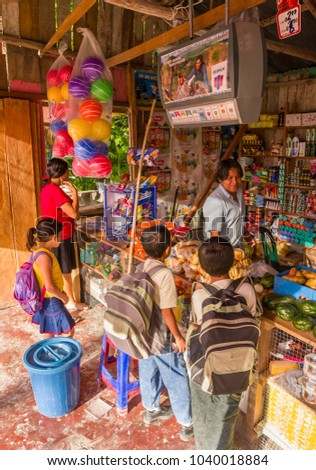REMATE, PETEN, GUATEMALA - AUGUST 12, 2008: School children shop at roadside independent store, early in the morning. #1040018884