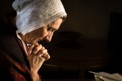 Rembrandt style or Renaissance portrait of a woman praying in a dark room