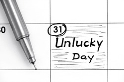 Reminder Unlucky Day in calendar with pen. Close-up