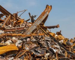 remnants of a fire, pile of burnt twisted steel against a blue sky, aftermath of a warehouse fire, corroded metal