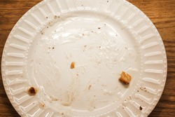 Remnants of cinnamon rolls on a dirty plate