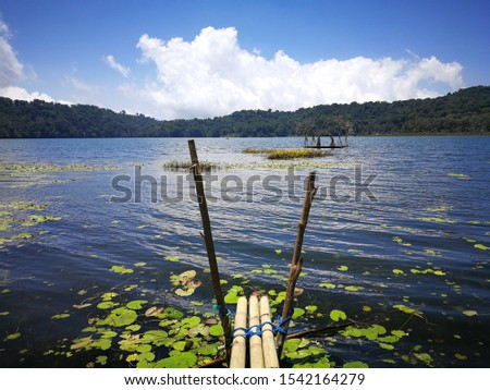 Remote and serene water landscape featuring a small fishers bridge reaching partly over a beautifully calm lake in the middle of Bali, Indonesia. Golden hour in nature #1542164279