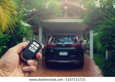 Remote car keys, and black car in the house background.
