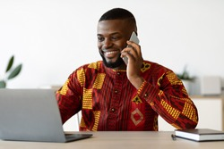 Remote Career. Young African Freelancer Man In Traditional Clothes Talking On Cellphone And Working On Laptop Computer At Home Office, Having Pleasant Conversation, Enjoying Distance Job, Copy Space