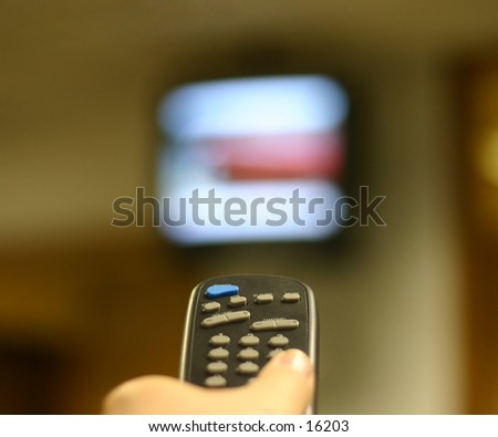 remote control in a hand pointing directly at a high mounted television set