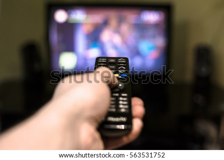 Remote control in hand in front of TV. Couch potato. #563531752