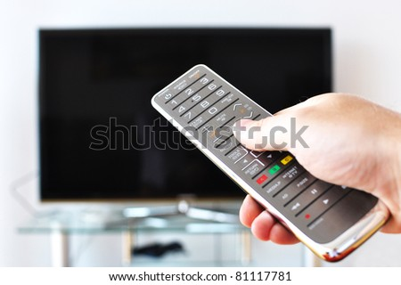 Remote control in the hand against TV screen