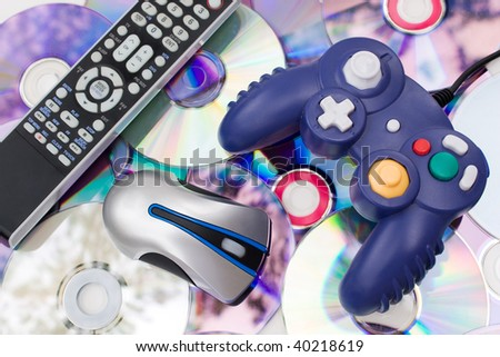 Remote control wireless computer mouse and video game controller over a bed of dvd disks isolated over white.