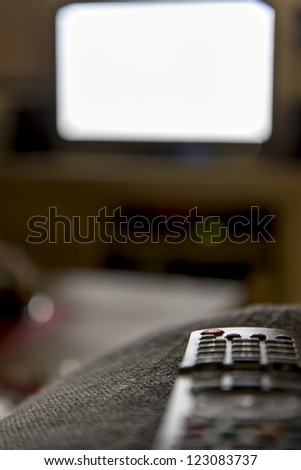 remote control with tv in the background