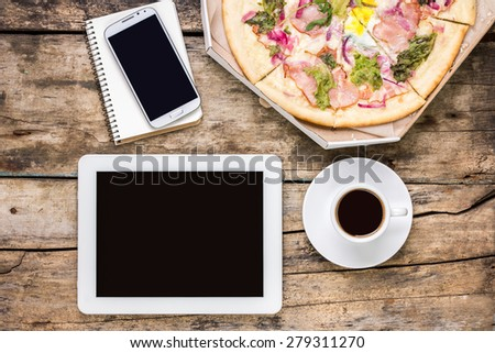 Remote freelance workplace coffee break. Outsource workspace with tablet PC, smartphone and pizza with coffee. Top view image