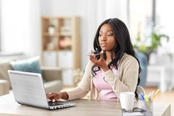 remote job, technology and people concept - african american young woman with laptop computer working at home office and using voice command recorder on smartphone