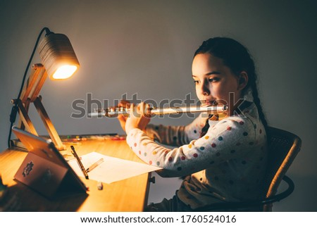 Remote music lesson. Girl playing the flute at home at the night. ストックフォト ©