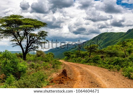 Remote rural area near Siracho Escarpment, Baringo County, Kenya looking across the Great Rift Valley. The rough dirt road is rocky and off the beaten track. Storm brewing. Natural landscape scenery.
