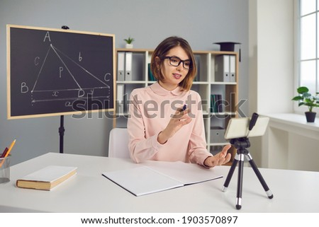 Remote teaching. College professor or school math teacher having online class, using mobile phone with tripod. Smart young woman in glasses explaining geometry problem in virtual lesson via video call