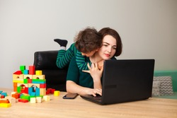 remote work at home. the son, the child sits out of boredom at the tired mother's neck, demanding the attention of the parent. A woman works at home at a computer