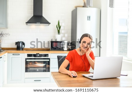 Remote work from home. Call-centre worker. Portrait of a young business woman working on laptop computer, talking online using a headset while sitting on the kitchen at home