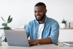 Remote Work. Handsome Black Freelancer Guy Working On Laptop At Home Office, Sitting At Desk With Computer, Smiling African American Man Looking At Device Screen, Enjoying Freelance Job, Copy Space