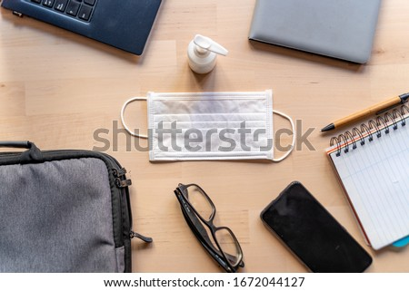 remote work kit on wooden office desk with hand sanitizer and face mask, a solution against the spread of corona virus for quarantined employees