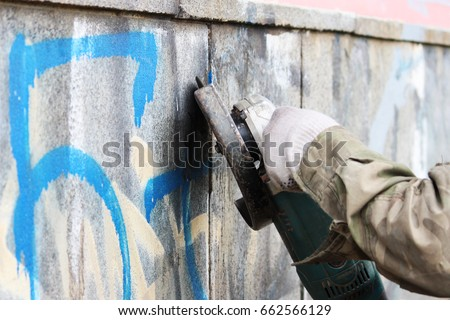 Removal of graffiti on a concrete wall of an underground passage with the help of a angle grinder. - Shutterstock ID 662566129
