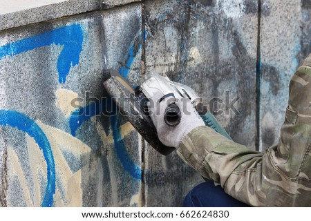 Removal of graffiti on a concrete wall of an underground passage with the help of a angle grinder - Shutterstock ID 662624830