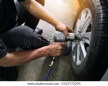Removing car mechanic to repair the leaky tire car wheels.Mechanic changing a car tire on a vehicle a hoist using an electric drill to loosen the bolts .concept of service or replacement.