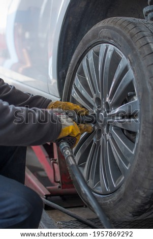 Removing car mechanic to repair the leaky tire car wheels.Mechanic changing a car tire on a vehicle a hoist using an electric drill to loosen the bolts .concept of service or replacement. Stok fotoğraf ©