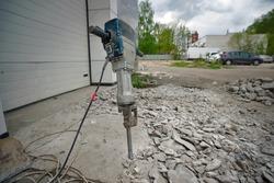 Removing concrete floor with jackhammer tool. Concrete rubble debris on construction site. Destruction of old concrete. Construction tools, jackhammer on the destroyed floor. Electric jackhammer.