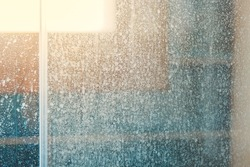 Removing hard water stains and deposits in bathroom. Stains drops on glass shower doors. Cleaning bathroom concept.
