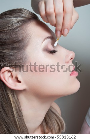 Removing makeup from face with cotton swab