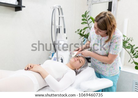 Removing wrinkles on the face and neck with massage. A beautiful blonde smooths wrinkles on the face and neck area with the help of massage in the beauty salon #1069460735