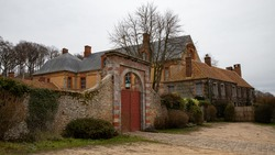 Renaissance castle (16th century) in northern France. Slate-tiled roof, yellow ocher facades with red bricks, large windows and tall brick chimneys. High surrounding wall with large red wooden gate