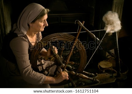 Renaissance Old Master portrait of a woman with antique spinning wheel in front of a fireplace