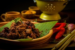 Rendang Daging Sapi or Beef stew traditional food from Padang, Indonesia. The dish is arranged among the spices and herbs used in the original recipe like chili, lemongrass onion