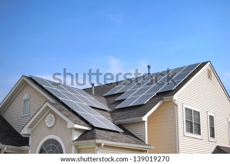 Renewable clean green energy saving efficient photovoltaic solar panels on multiple gable suburban house roof over blue sky