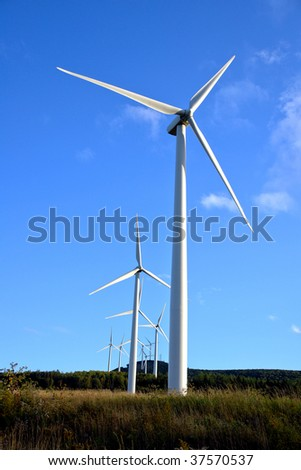 Renewable energy wind turbines farm with electric power generation windmills generating electricity on a hill over blue sky