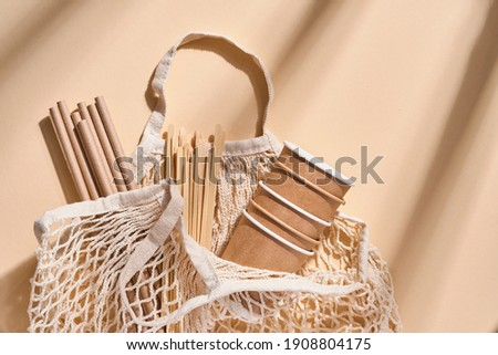 Renewable individual objects for home use, bamboo or paper straws, disposable cups and wooden coffee stirrers on beige with shade from the leaves on the beach. Zero waste. Pollution environment. Top Photo stock ©