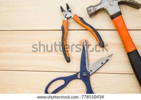 Renovating a house. A set of bright repair tools -pilers, scissors and a hammer on a light uncolored wooden background, close up. Top view. Space for your text or pruduct display. #778550434