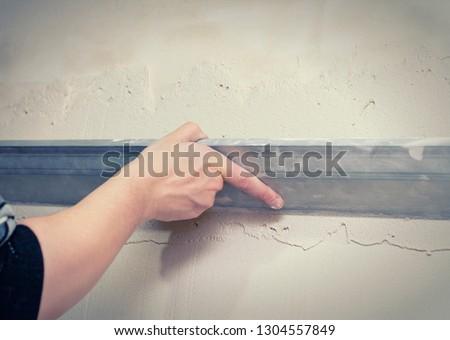 Renovation at home. Plasterer spreading plaster on wall. Who plaster wall plaster master. #1304557849