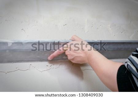 Renovation at home. Plasterer spreading plaster on wall. Who plaster wall plaster master. #1308409030