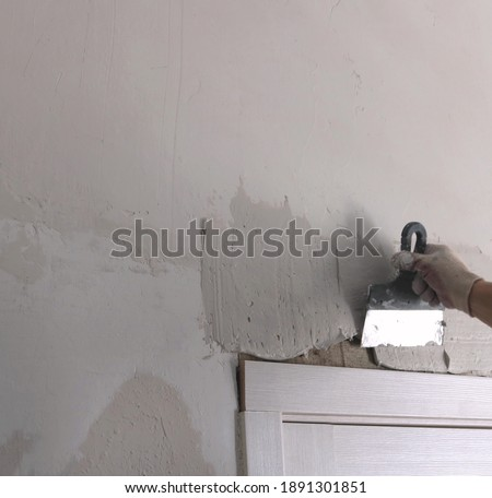 renovation construction background with a gloved hand of a builder applying a layer of plaster to the top of the door jamb using a metal trowel with empty copy space on the left Photo stock ©