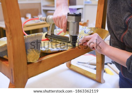 Renovation of old upholstery. Woman hands working in upholstery workshop. Making new upholstery on old chair. Yellow fabric. Work with pneumatic stapler.  Stockfoto ©
