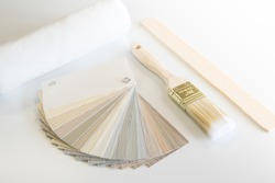 Renovation or home improvement items including a siding color sampler, paint brush, roller sleeve and stir stick on white