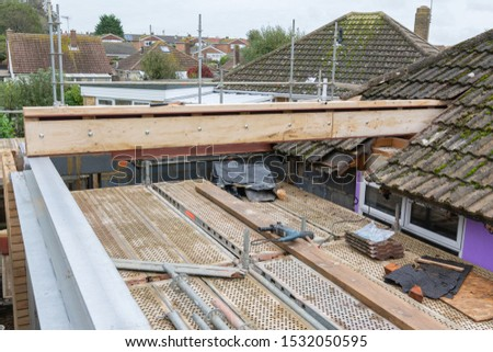 Renovation projects. Building of extension of the existing house, unfinished wooden roof structure, steel beams,brick walls. steel beams, selective focus #1532050595