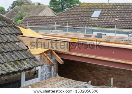Renovation projects. Building of extension of the existing house, unfinished wooden roof structure, steel beams,brick walls. steel beams, selective focus #1532050598