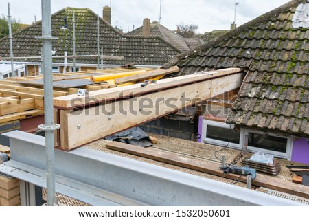 Renovation projects. Building of extension of the existing house, unfinished wooden roof structure, steel beams,brick walls. steel beams, selective focus #1532050601