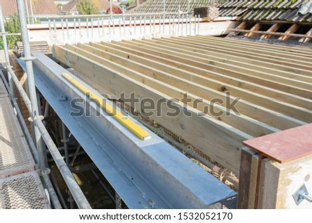 Renovation projects. Building of extension of the existing house, unfinished wooden roof structure, steel beams,brick walls. steel beams, selective focus #1532052170